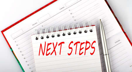 NEXT STEPS text on notebook on diary, business