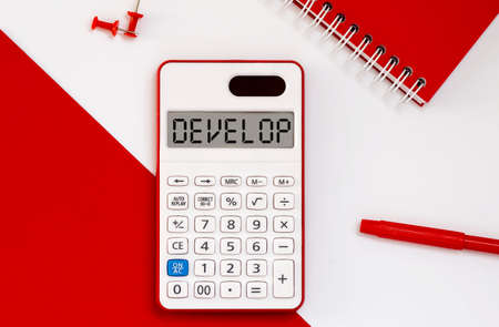 calculator with the word DEVELOP on display with red notepad and office tools