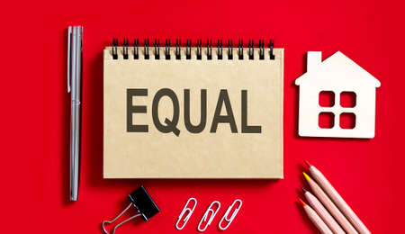 EQUAL text written on notebook with pencils and office tools and model wooden house