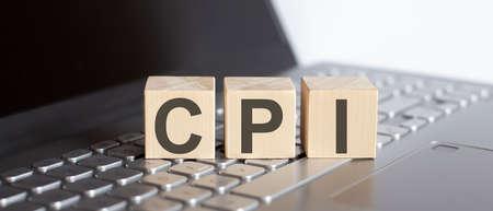 CPI abbreviation written on wooden cube on laptop Reklamní fotografie