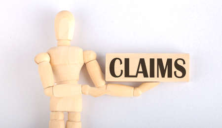 Wooden man shows with hand to block with text CLAIMS Banque d'images