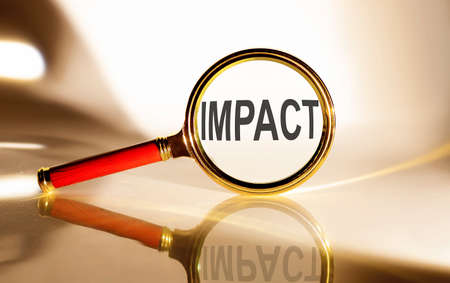 IMPACT concept. Magnifier glass with text on the white background in sunlight. Banco de Imagens