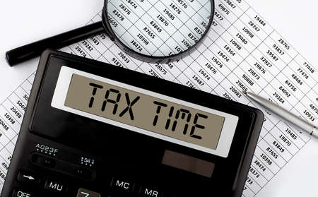 Word TAX TIME on calculator. Business and tax concept.