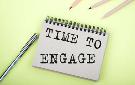 TIME TO ENGAGE text on the notebook with pen on the yellow background