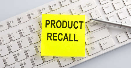 Words PRODUCT RECALL written on stickers on computer keyboard