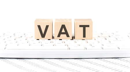 VAT -word wooden block on the keyboard background witn chart