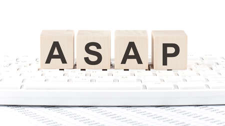 ASAP -word wooden block on the keyboard background witn chart