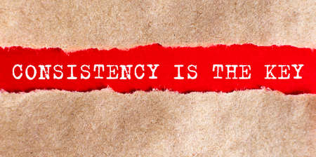 Consistency is The Key appearing behind torn paper on the red background