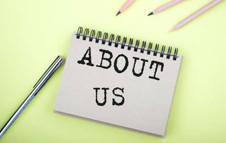 ABOUT US text on notebook with pen on yellow background