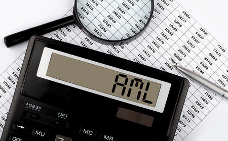 Calculator with text AML on chart. Business, finance conceptual. Stock Photo