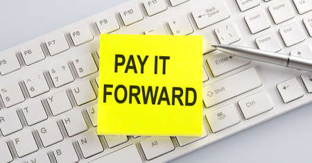 text PAY IT FORWARD on the keyboard on white background