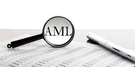Magnifying glass with text ANTI MONEY LAUNDRING on the chart background with pen Stock Photo