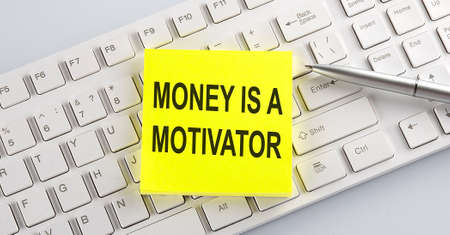 text MONEY IS A MOTIVATOR on keyboard on the white background