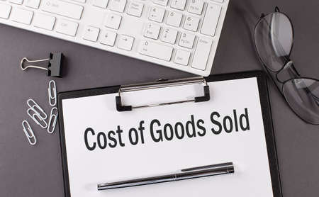 Office paper sheet with text COST OF GOODS SOLD with office tols and keyboard. Business