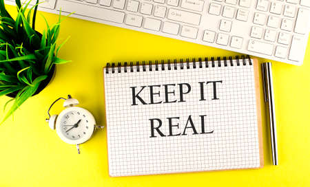 KEEP IT REAL text on notebook with keyboard, pen and alarm clock on yellow background Standard-Bild