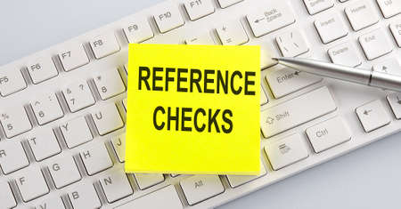 Words REFERENCE CHECKS written on stickers on computer keyboard Foto de archivo