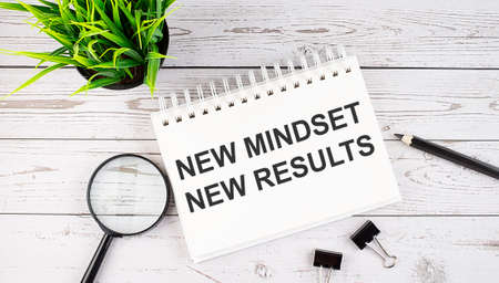 NEW MINDSET NEW RESULT text concept write on notebook with office tools on wooden background