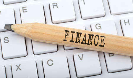 Text FINANCE on wooden pencil on white keyboard. Business