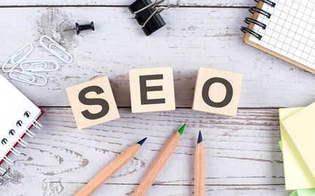 SEO text on wooden block with office tools on the wooden background Stock Photo