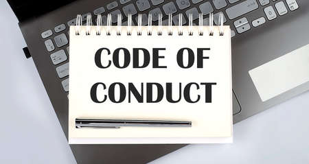 CODE OF CONDUCT - Top view notebook writing on laptop Banque d'images