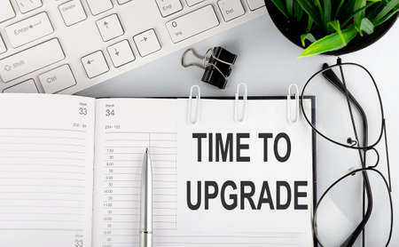 Text TIME TO UPGRADE on calendar planner to remind you an important appointment with pen and keyboard on white background.