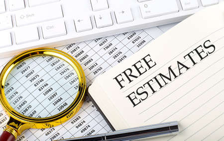 FREE ESTIMATES text on the notebook with chart, magnifier, keyboard and pen