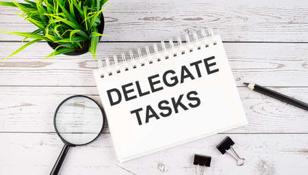 DELEGATE TASKS text concept write on notebook with office tools on the wooden background