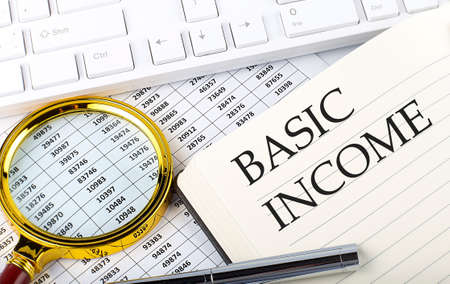 BASIC INCOME text on the notebook with chart, magnifier, keyboard and pen