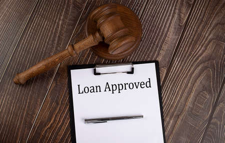 LOAN APPROVED text on the paper with gavel on the wooden background Stock Photo