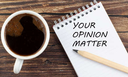 YOUR OPINION MATTER text on notebook with coffee on the wooden background 写真素材
