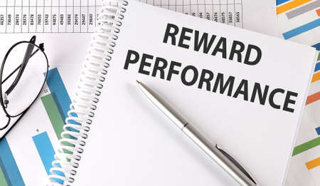 REWARD PERFORMANCE text, pen and glasses on the chart, business