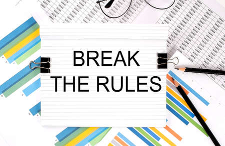 Notebook with pencils, glasses on graph background, with text BREAK THE RULES Foto de archivo