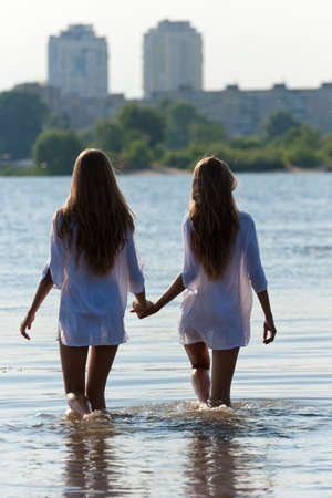 Young woman twins in water and blurred buildings on background