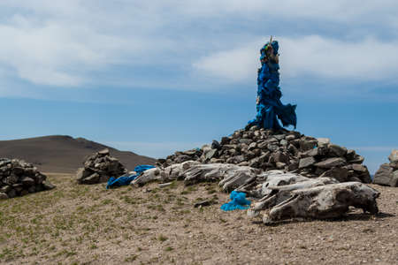 Oovoo (ovoo) - Mongolian stone shrine for travelers, with ceremonial prayer flags or scarves (khadag) and horse skulls