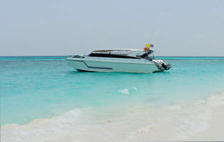 White speedboat on tropical beach. Emerald water of Andaman sea Imagens