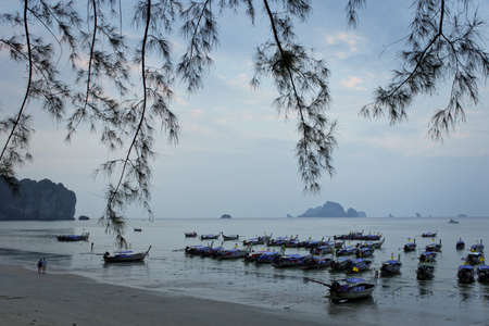 Tropical evening after sunset. Ocean tide with thai longtail boats and island silhouettes on background Stock Photo