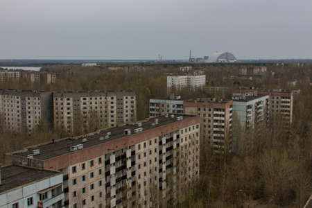 View of the empty buildings in dead city Pripyat, from above. Chernobyl Nuclear Power Plant sarcophagus on horizon view Stock Photo