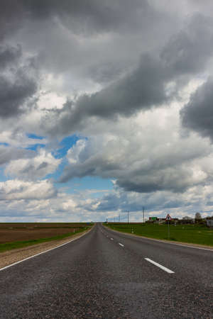 Road near small village, and dramatic stormy sky Stock Photo