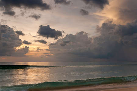 Tropical sunset, ocean waves and cloudy sky. Thailand
