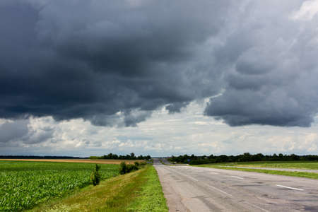 Road between fields, and dramatic rainy sky
