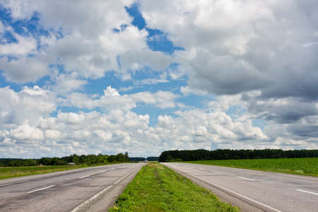 Road between fields, and beautiful cloudy sky Stock Photo