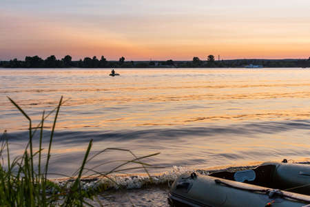 Beautiful sunset on Dnipro river and fishing boat on foreground