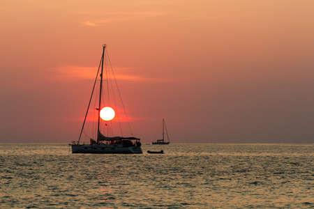 Sunset in Nai Harn beach and sailboat silhouette. Phuket, Thailand.