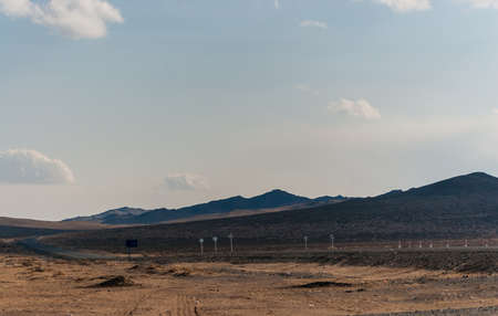 Road among the hills in Mongolian wild steppe. Mountains on horizon and cloudy sky