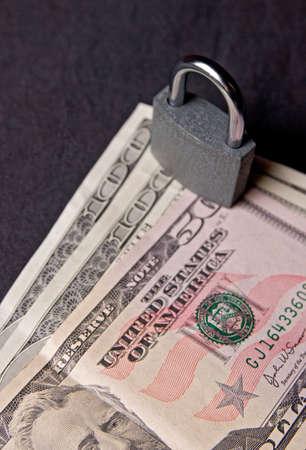 Closed padlock staying on US dollars, on dark background