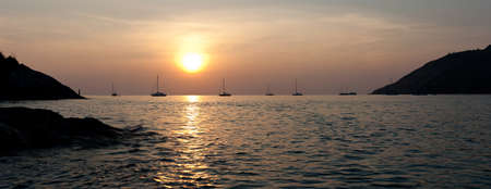 Panorama view on sunset in Nai Harn cove and sailboats silhouettes. Phuket, Thailand