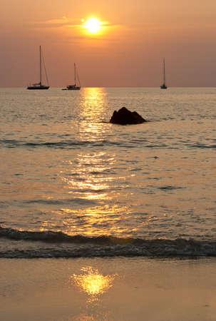 Sunset in Nai Harn beach and sailboats silhouettes. Phuket, Thailand Stock Photo