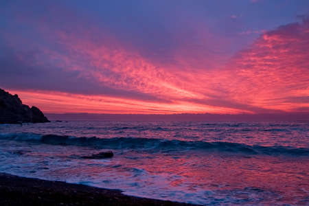 Early winter morning in Crimea bay. Waves on morning pink sky background.