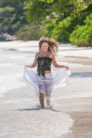 Young beautiful woman runs on a tropical beach Standard-Bild