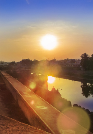 sunspot: Sunset sky of multiple colors over the small city Fort scaterred rays of lights,flare and its reflection on water.South-East Asia.South India.The Fort was made 1400Years ago by some South Indian King.East-INdia conpany  had a major ruling power from this